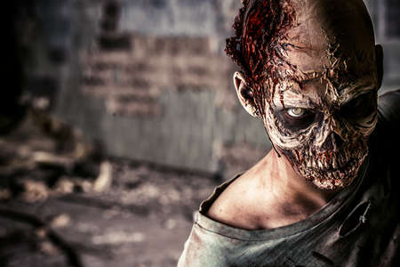 apocalypse: Horrible scary zombie man on the ruins of an old house. Horror. Halloween.