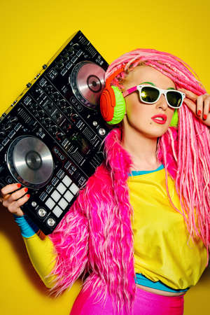 crazy girl: Expressive modern DJ girl wearing bright clothes, headphones and bright dreadlocks mixing up some music. Disco, party. Modern generation.