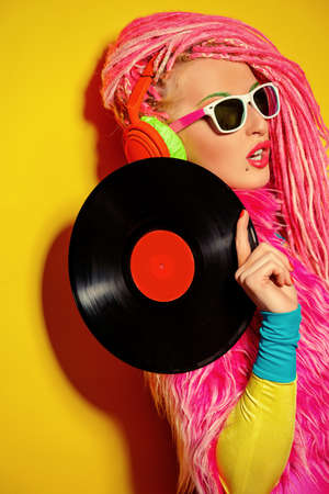 ultra modern: Glamorous modern DJ girl posing with vinyl record. Disco, party. Bright fashion.