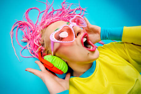 crazy girl: Crazy expressive trendy DJ girl in bright clothes, headphones and bright dreadlocks. Disco, party. Bright fashion.