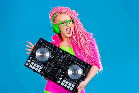 modern generation: Muchacha expresiva DJ moderno vistiendo ropa brillante, auriculares y rastas brillantes mezcla un poco de m�sica. Disco, fiesta. Generaci�n moderna.