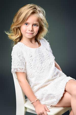 petite fille avec robe: Mode tir d'une jolie petite fille avec de beaux cheveux blonds portant robe blanche.