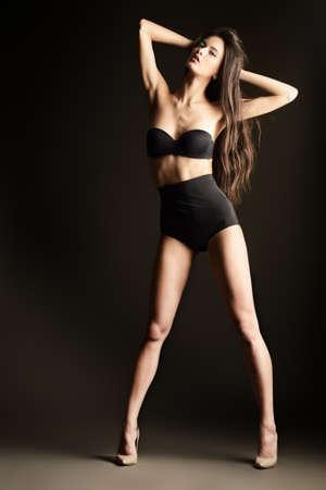 alluring women: Beautiful slender woman alluring in black sexy lingerie. Fashion studio shot. Stock Photo