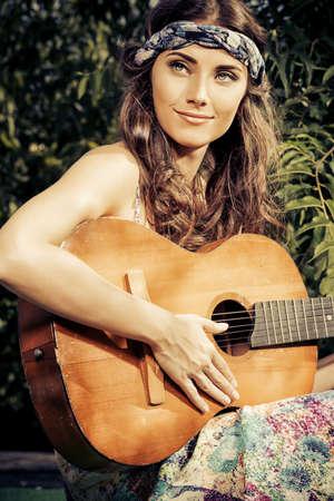 cintillos: Chica hippie alegre que toca la guitarra al aire libre en el día soleado de verano. Niño de la naturaleza. Estilo de vida. Foto virada, sepia.