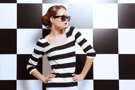 stile: Bella modella posa in abito a strisce bianche e nere su uno sfondo di quadrati bianchi e neri. Bellezza, concetto di moda. Stile di affari.