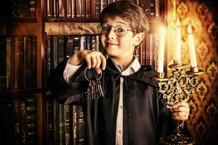libros antiguos: Muchacho emocional se coloca con un manojo de llaves antiguas y velas en la biblioteca con muchos libros antiguos. Cuentos de hadas. Estilo vintage.