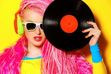 Glamorous moderna Muchacha de DJ que presenta con el disco de vinilo. Disco, fiesta. Bright fashion.