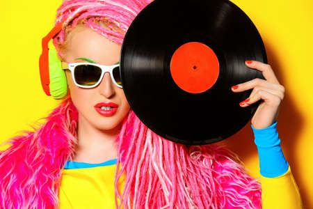 Glamorous modernen DJ Mädchen posiert mit Vinyl-Schallplatte. Disco, Party. Helle Mode.