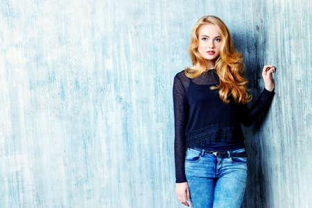 moda ropa: Hermosa chica rubia en ropa de jeans posando junto a la pared del grunge. Moda.