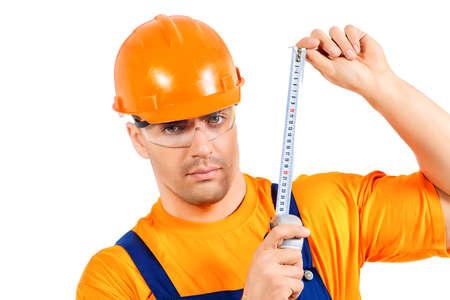 obrero trabajando: Un trabajador de la construcción que trabajan con cinta métrica. Trabajo, ocupación. Aislado en blanco.