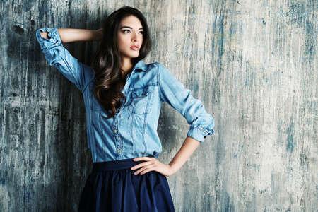 mode: Mooie sensuele vrouw in jeans kleding staat door de grunge muur. Fashion.