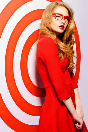 red dress: Gorgeous fashion model in red dress and elegant red glasses posing over red circles of the target. Beauty, fashion. Optics, eyewear.