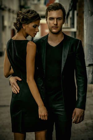 black suit: Fashion style photo of a beautiful couple over city background. Stock Photo