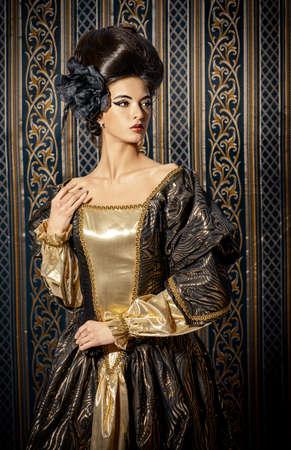 princesa: Barroco - joven y bella mujer en traje histórico elegante y con el peinado barroco que presenta sobre el fondo de la vendimia. Renacimiento. Barocco. Moda.