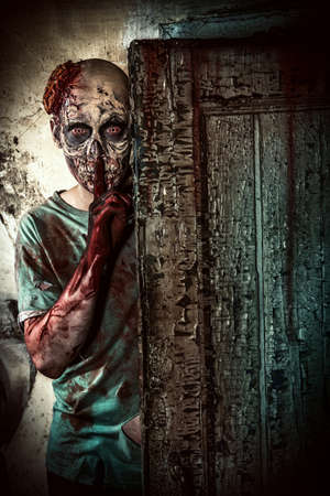 Hrozné děsivý zombie muž na troskách starého domu. Horor. Halloween.