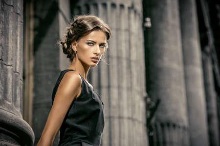 Modelo de Vogue con un vestido negro posando sobre fondo urbano. Disparo de moda. Foto de archivo