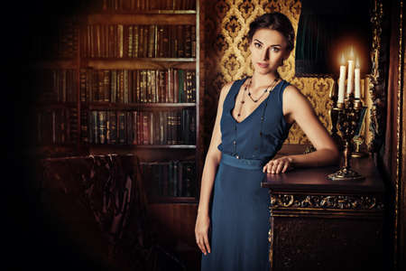 anochecer: Señora elegante con vestido de noche que se coloca en la habitación con interior clásico de la vendimia. Belleza, la moda.