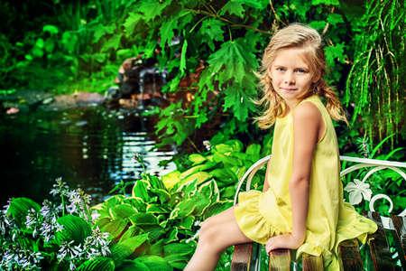 mignonne petite fille: Jolie jeune fille souriante au repos dans le parc de l'été. Enfance heureuse. Vacances.