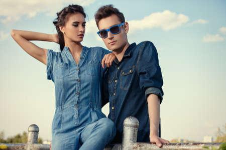 moda: Mavi gökyüzünün üzerinde kot elbise giyen modern gençlerin portresi. Moda atış.