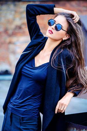 modelo: Modelo de mujer de moda al aire libre de fascinación por la pared de ladrillo. Estilo de la ciudad. Foto de moda.