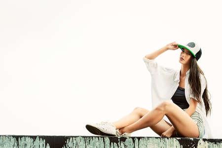 stile: Ragazza moderna indossando abiti casual e un berretto posa all'aperto. Ragazza adolescente. stile giovanile. Fashion style.