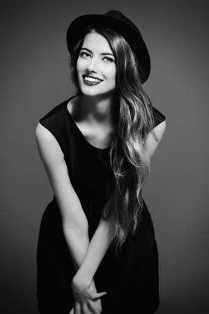 Joyful hübsches Mädchen mit schwarzen Kleid und schwarzen klassischen Hut Lächeln in die Kamera. Beauty, Fashion-Konzept. Hipster-Stil.
