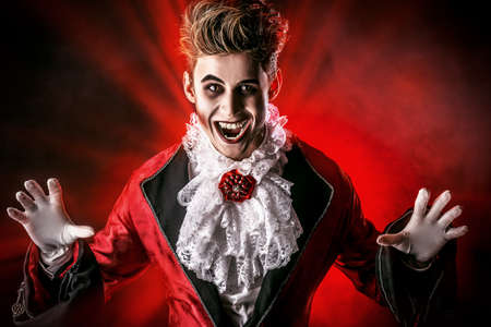 halloween backgrounds: Handsome bloodthirsty vampire in Dracula costume.