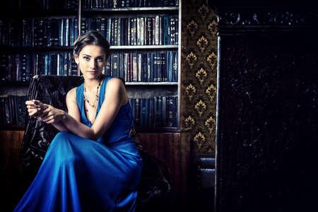 anochecer: Señora elegante con vestido de noche sentado en la silla en la antigua biblioteca de la vendimia
