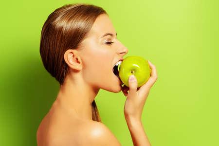manzana verde: Muchacha bonita morder la manzana fresca sobre fondo verde