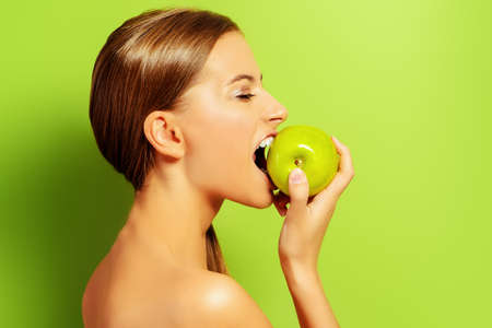 summer diet: Pretty girl biting fresh apple over green background