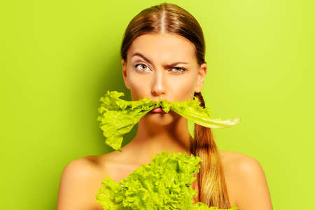 vegan food: Pretty cheerful young woman posing with fresh green lettuce leaves