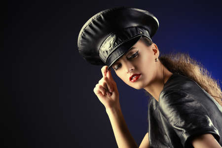 Sexual young woman alluring in fitting leather suit and a cap of police officer Stock Photo