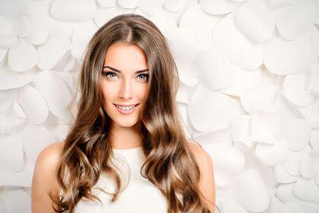 szépség: Gyönyörű pályázati nő fehér ruhában pózol a háttérben fehér papír virágok
