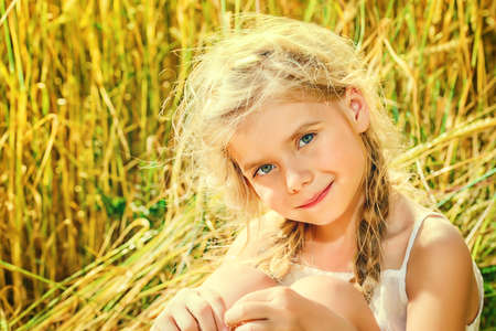 sincere girl: Smiling little girl with beautiful blonde hair sitting in the wheat field on a bright sunny day