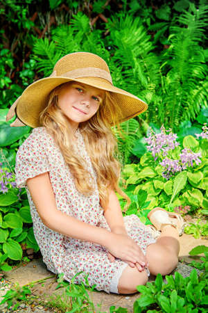 pretty young girl: Little elegant girl resting in a beautiful summer park Stock Photo