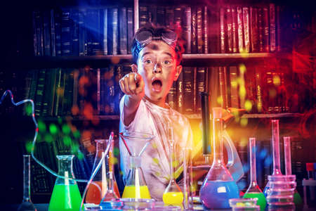 school boy: A boy doing experiments in the laboratory. Explosion in the laboratory Stock Photo