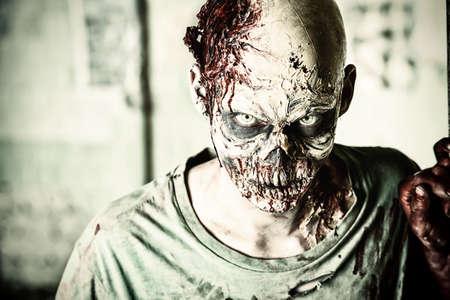 Hrozné děsivý zombie muž na troskách starého domu