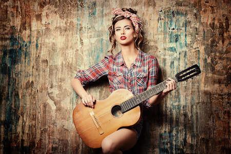 Hübsches Pin-up-Mädchen, das mit Gitarre aufwirft