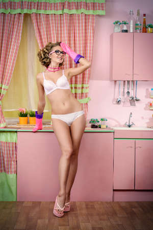 girl panties: Beautiful girl in sexy lingerie alluring on her glamorous pink kitchen. Fashion. Full length portrait. Stock Photo