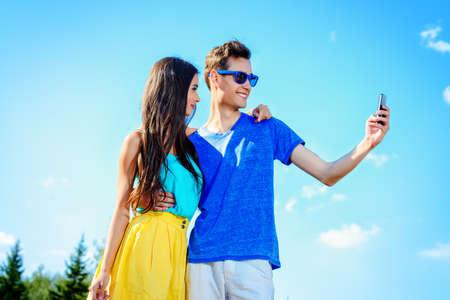 mujer sexy: Feliz pareja joven caminando en el parque y hacer selfie por tel�fono inteligente. Feliz d�a de verano. Foto de archivo