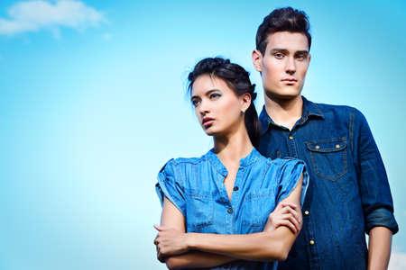 Retrato de una moderna jóvenes que vestían ropa de jeans en el cielo azul. Disparo de moda. Foto de archivo