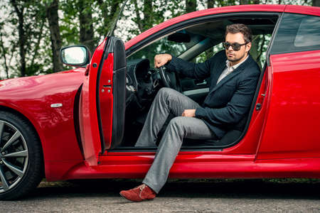 Pohledný mladý muž v jeho novém sportovním autě. Reklamní fotografie