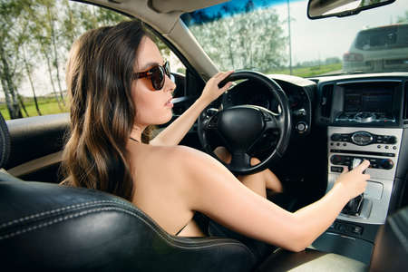 Beautiful young woman driving her car. Beauty, fashion. Luxurious life.