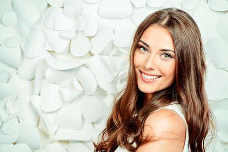 Schöne zarte Frau im weißen Kleid posiert mit dem Hintergrund der weißen Papierblumen. Schönheit, Mode. Haarpflege. Cosmetics. Standard-Bild