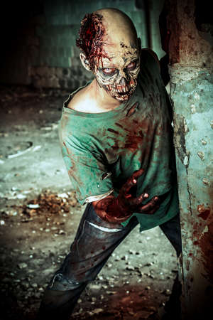 face zombie: Horrible scary zombie man on the ruins of an old house. Horror. Halloween.