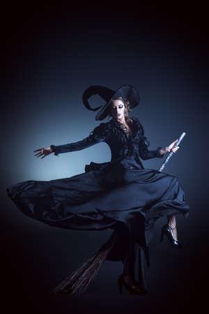 Porträt einer wunderschönen Brünette Hexe fliegt auf einem Besen über schwarzen Hintergrund. Halloween.