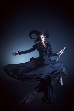 escoba: Retrato de una hermosa bruja morena volando en una escoba sobre fondo negro. Halloween.