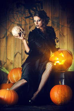 wiedźma: Atrakcyjne czarownica dziewczyna w czarnej sukni trzyma czaszkę w tajemniczej opuszczonym domu. Czary, czarownica. Wampir. Koncepcja Halloween.