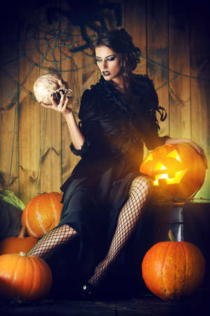 female vampire: Attractive witch girl in black dress holding a skull in a mysterious abandoned house. Witchcraft, witch. Vampire.  Halloween concept. Stock Photo