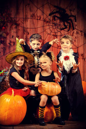halloween: Cheerful children in halloween costumes celebrating halloween in a wooden barn with pumpkins. Halloween concept.